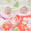 紫と赤い祝い着(産着)を着た赤ちゃん
