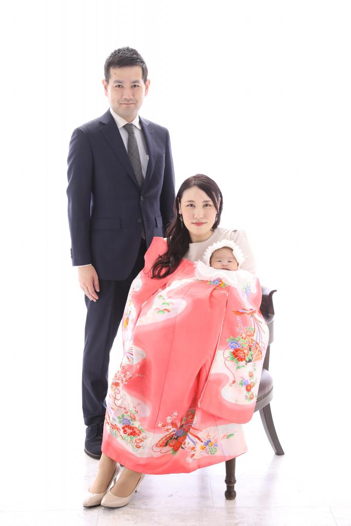 赤い産着を着た女性と赤ちゃんとスーツを着た男性