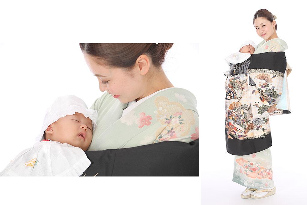 黒い産着と薄い緑色の訪問着を着た女性と赤ちゃん