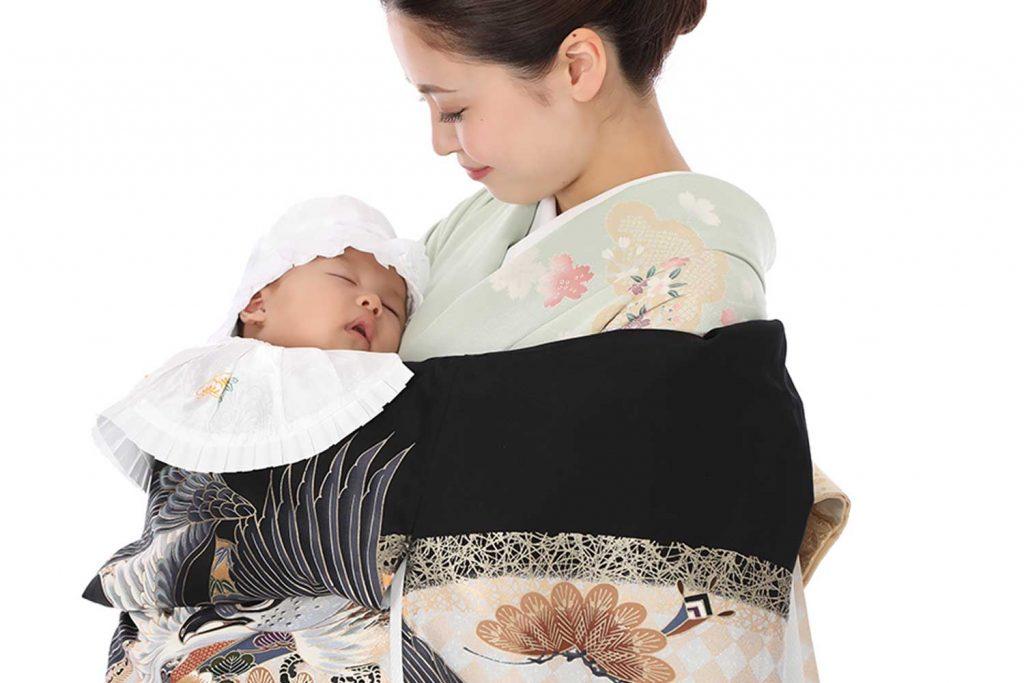お宮参りの産着と訪問着を着た女性と赤ちゃん