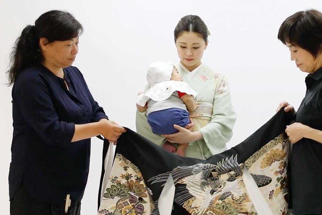 産着を女性にかぶせている写真