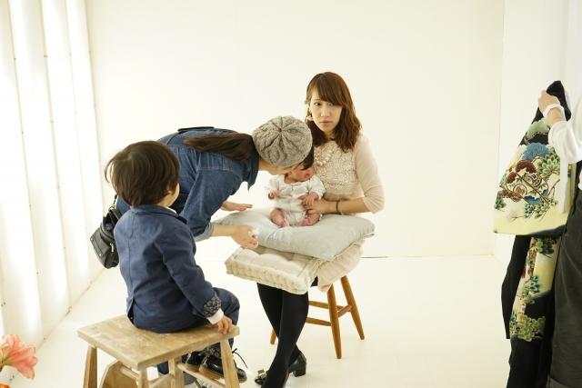 赤ちゃんを抱っこして椅子に座っている女性と、撮影のセッティングをする女性