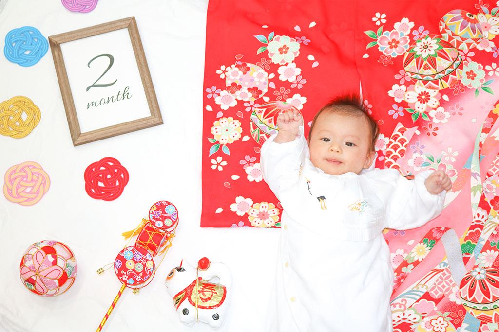 赤の花柄の産着で寝相アートを撮る赤ちゃん