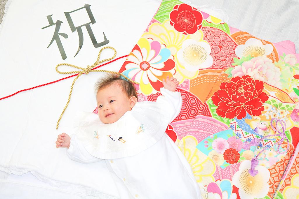 オレンジ色の花柄の産着で寝相アートを撮る赤ちゃん