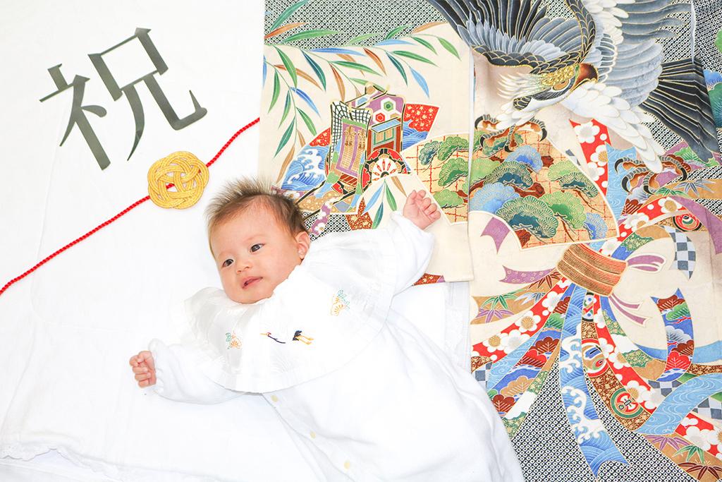 黒い鷹柄の産着で寝相アートを撮る赤ちゃん