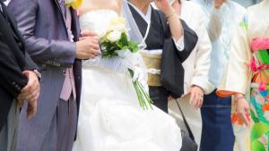 タキシードを着た男性とウエディングドレスを着た女性と黒留袖を着た女性と振袖を着た女性
