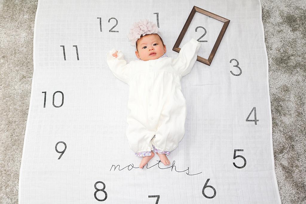 時計をモチーフにした寝相アートを撮る赤ちゃん