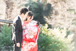 お宮参りの産着を着た女性とスーツを着た男性