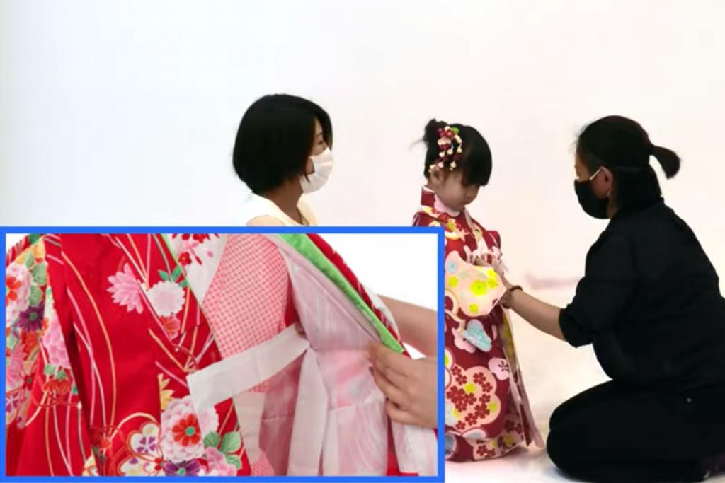 七五三の3歳女の子の着物の着付けをする女性と着付けてもらっている女の子