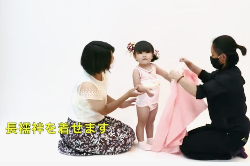 三歳女の子に長襦袢を着せている女性