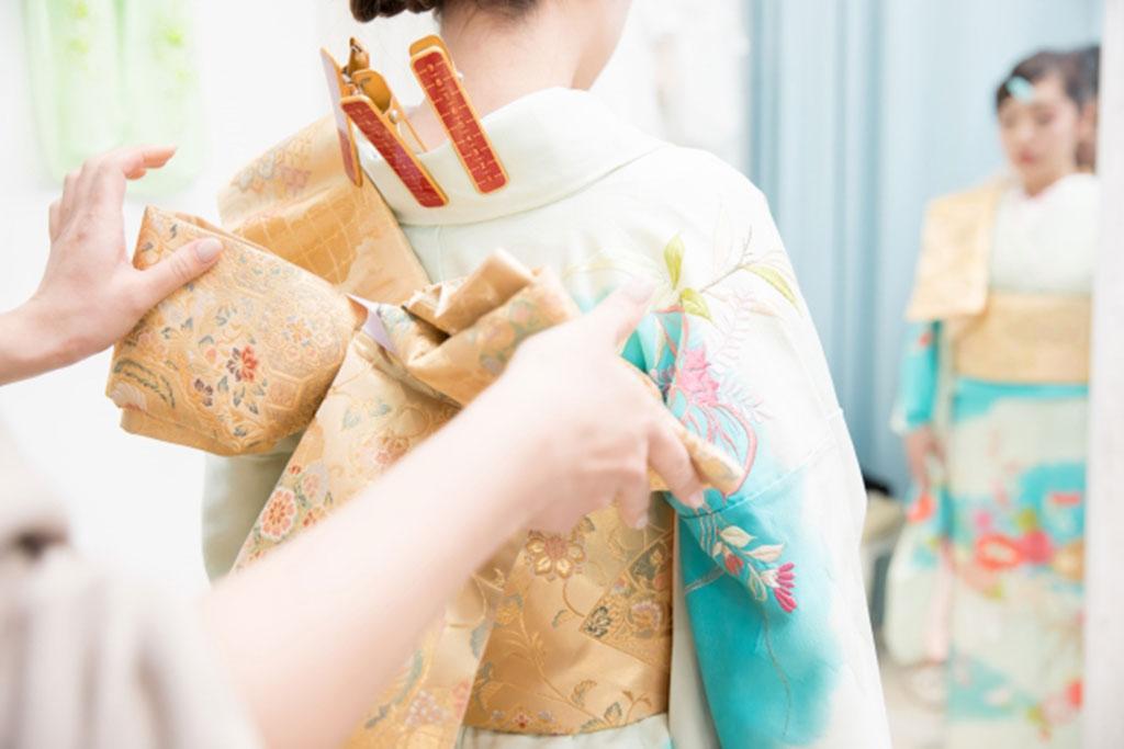 振袖の着付けをする女性