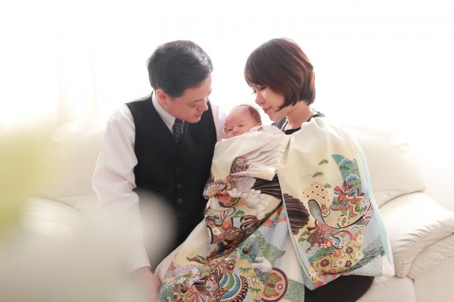 白い産着を着た母親と赤ちゃんとスーツを着た父親