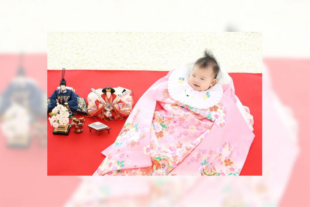 初節句を祝うピンクの被布を着た赤ちゃんと雛人形