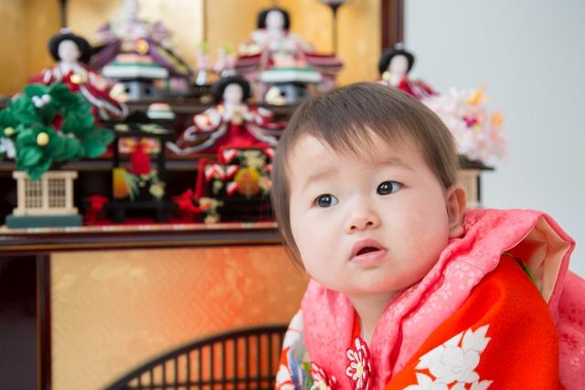 赤い被布を着た赤ちゃんと雛人形