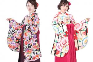黒い着物にエンジの袴を着た女性と白い着物にピンクの袴を着た女性