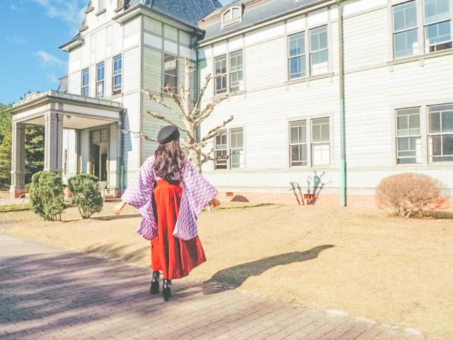 紫の矢絣の着物にオレンジ色の袴を着た女性