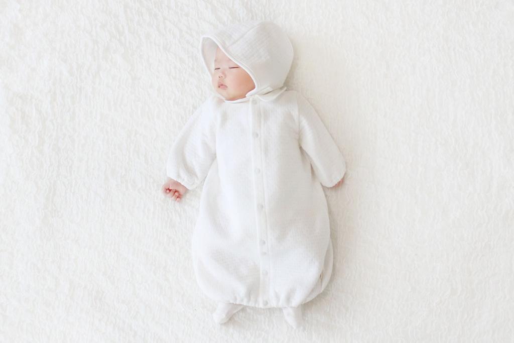 白い2wayオールのベビードレスを着て眠っている赤ちゃん