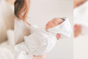 白い2wayオールのベビードレスを着た赤ちゃんと抱っこしている母親