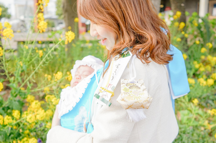 水色の産着を着用して赤ちゃんを抱っこする女性