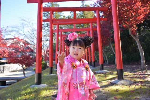 神社の鳥居の前でピンクの着物を着た女の子