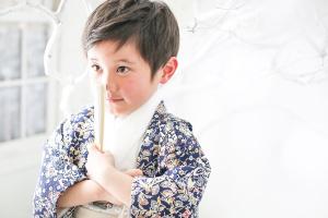 紺色の羽織に白い着物と袴を着て白いセンスを持った男の子