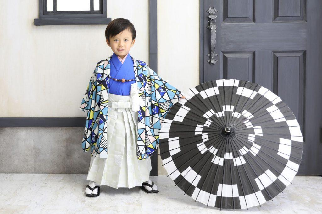 水色と白と青のステンドグラス柄の羽織に青い着物と白い袴の羽織袴を着た男の子と白と黒の番傘