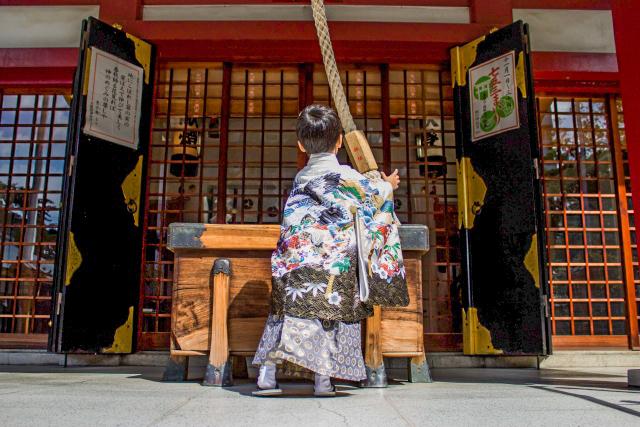 白の羽織袴を着て神社参拝をする男の子