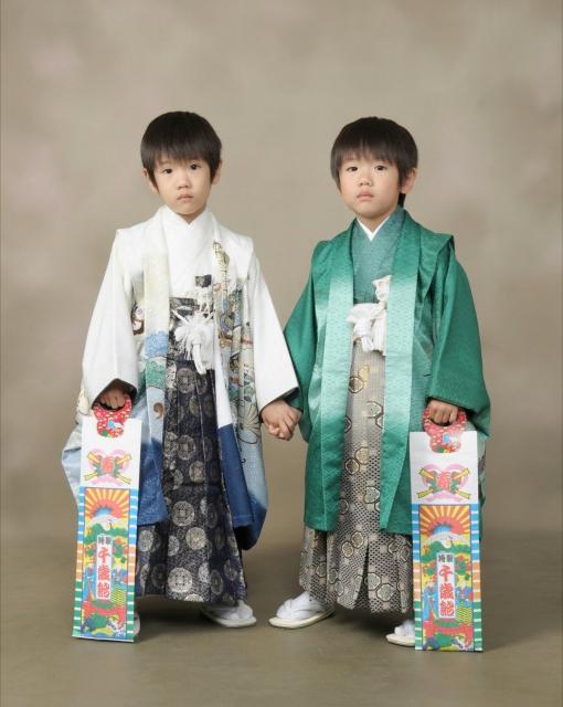 白い羽織袴を着た男の子と緑色の羽織袴を着た男の子