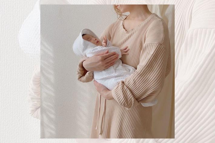 ベージュのワンピースを着た女性が 白いベビードレスを着た赤ちゃんを抱っこ